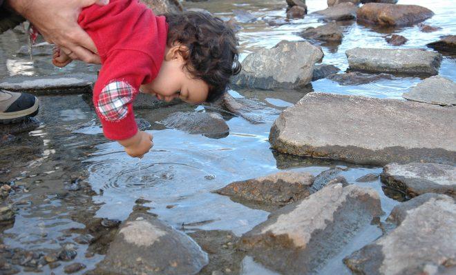 Daniel tocando el agua del lago