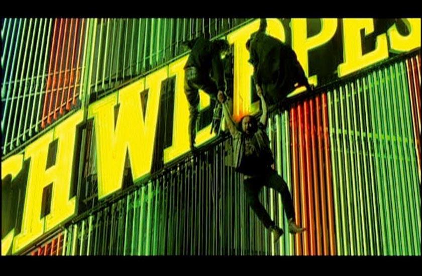 Santiago Segura colgando del cartel Schweppes